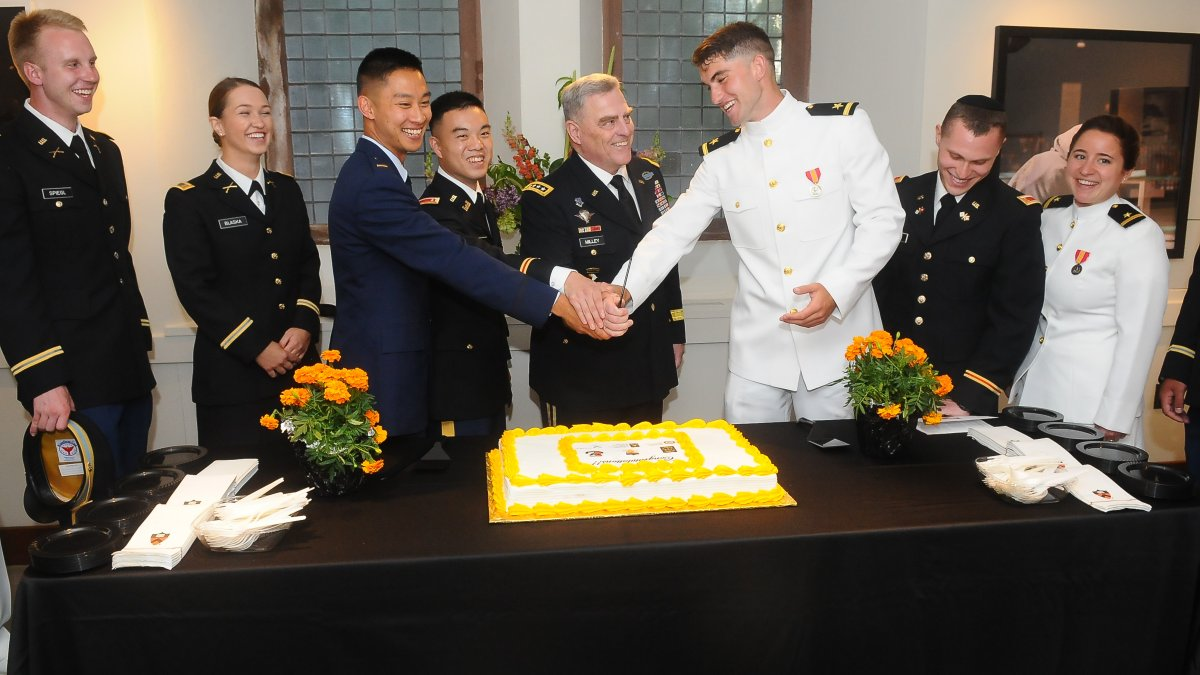 General Mark A. Milley '80 gets prepared to cut the commissioning cake with the newest 2nd Lieutenants and Ensigns.